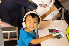 Asian kid play computer internet games and wear headset. To communicate Stock Photo