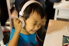 Asian kid play computer internet games and wear headset Stock Photo