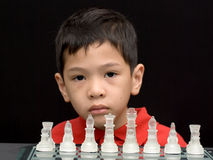 Asian kid playing chess. Another pose of an asian kid playing chess is waiting for his/her opponent to move Stock Image