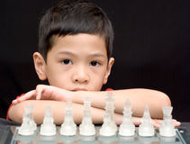 Asian kid playing chess. An asian kid playing chess is waiting for his/her opponent to move Stock Image