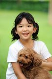 Asian kid playing with dog. Asian kid sitting and holding poodle dog Stock Image