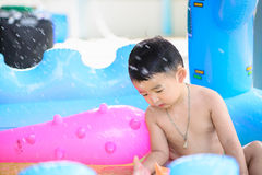 Asian kid playing in inflatable baby swimming pool on hot summer. Asian kid playing in inflatable baby pool. Boy swim and splash in colorful swimming pool with stock image