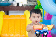 Asian kid playing in inflatable baby swimming pool on hot summer. Asian kid playing in inflatable baby pool. Boy swim and splash in colorful swimming pool with stock photography
