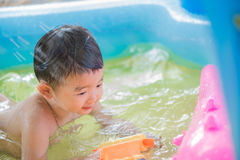 Asian kid playing in inflatable baby swimming pool on hot summer Royalty Free Stock Photo