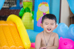 Asian kid playing in inflatable baby swimming pool on hot summer Royalty Free Stock Image