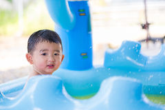 Asian kid playing in inflatable baby swimming pool on hot summer Royalty Free Stock Images