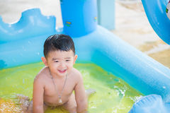 Asian kid playing in inflatable baby swimming pool on hot summer Stock Photography