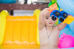 Asian kid playing in inflatable baby swimming pool on hot summer Royalty Free Stock Photography
