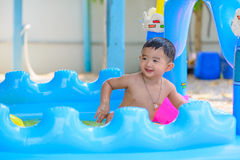 Asian kid playing in inflatable baby swimming pool on hot summer. Asian kid playing in inflatable baby pool. Boy swim and splash in colorful swimming pool with royalty free stock photography