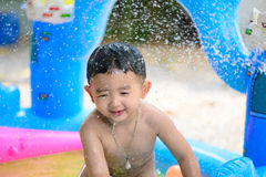 Asian kid playing in inflatable baby swimming pool on hot summer. Asian kid playing in inflatable baby pool. Boy swim and splash in colorful swimming pool with stock images