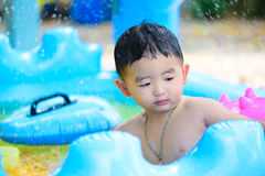 Asian kid playing in inflatable baby swimming pool on hot summer. Asian kid playing in inflatable baby pool. Boy swim and splash in colorful swimming pool with royalty free stock images