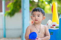 Asian kid playing in inflatable baby swimming pool on hot summer. Asian kid playing in inflatable baby pool. Boy swim and splash in colorful swimming pool with stock photo