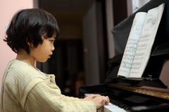 Asian kid playing piano. A little Chinese kid learning to play piano Stock Photography