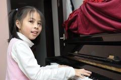 Asian kid playing piano Royalty Free Stock Photos