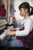 Asian kid playing piano Royalty Free Stock Photography