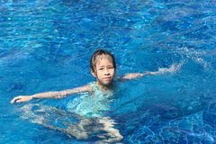 Asian kid playing in swimming pool Royalty Free Stock Image