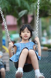 Asian kid playing on swing Stock Image