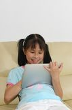 Asian kid playing with touchscreen Royalty Free Stock Photography