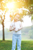 Asian kid playing windmill outdoors. Royalty Free Stock Image