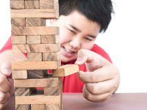 Asian kid is playing a wood blocks tower game stock images
