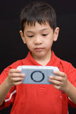 Asian kid portable console. An asian kid concentrated on playing a portable console Royalty Free Stock Photography