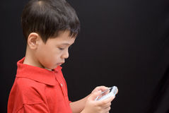 Asian kid portable console. Another side view of an asian kid concentrated on playing a portable console Stock Photos