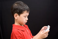 Asian kid portable console. A side view of an asian kid concentrated on playing a portable console Stock Image