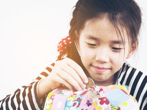 Asian kid is putting money in to a colorful piggy coin bank Royalty Free Stock Images