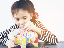 Asian kid is putting money in to a colorful piggy coin bank Stock Image