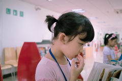 Asian kid reading book. A little Chinese kid reading book in the library Stock Image