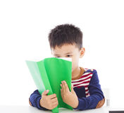 Asian kid reading a book. Over white background Royalty Free Stock Images