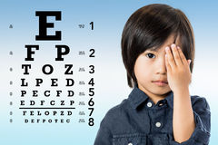 Asian kid reviewing eyesight. Close up portrait of little Asian boy reviewing eyesight. Kid closing one eye with hand and  alphabetical eye test chart in Stock Image