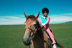 Asian kid riding horse. An Asian kid  riding horse on the grassland Royalty Free Stock Photography