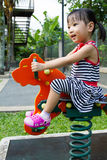 Asian Kid Riding at Park. Asian Chinese little girl riding trojan horse at park Royalty Free Stock Photo