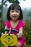 Asian Kid Riding at Park. Asian Chinese little girl riding trojan horse at park Royalty Free Stock Photos