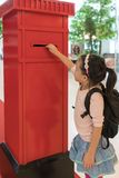 Asian kid sending her mail in the red mailbox royalty free stock photography