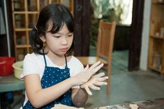 Asian kid shaping pottery Royalty Free Stock Image