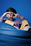 Asian kid sitting on a bean bag with hands in-front. focus on hands. Stock Photos