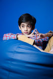 Asian kid sitting on a bean bag with hands in-front. focus on hands. Stock Photo