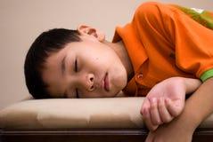 Asian kid sleeping. An asian kid fell asleep on a bench Stock Photo