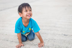 Asian kid smile. Happy asian kid smile sitting on driveway Royalty Free Stock Image