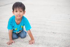 Asian kid smile. Happy asian kid smile sitting on driveway Royalty Free Stock Photo
