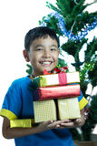 Asian kid smile holding stack of presents boxes. On white background Royalty Free Stock Photo