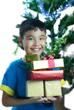 Asian kid smile holding stack of presents boxes. On white background Royalty Free Stock Photos