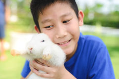 Asian kid smile and play with rabbit outdoor , selective focus. Asian kid smile and play with rabbit outdoor , selective focus at rabbit Stock Photography