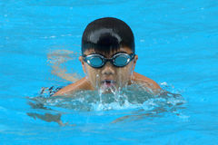 Asian kid swims in swimming pool - butterfly style take deep breath. Asian boy hard swiming training in swimming pool - butterfly style, face facing up and take Royalty Free Stock Photography