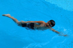 Asian kid swims in swimming pool - front crawl style Stock Photos