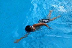 Asian kid swims in swimming pool - front crawl style with power scissor kick. Asian boy swims in swimming pool - front crawl style, face facing up and take royalty free stock images