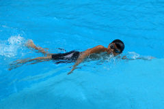 Asian kid swims in swimming pool - front crawl style with power scissor kick. Asian boy swims in swimming pool - front crawl style, face facing up and take royalty free stock image