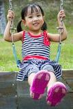 Asian Kid Swing At Park Royalty Free Stock Photo